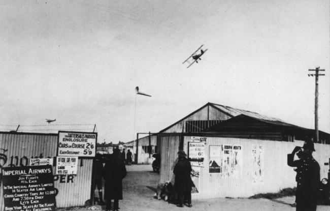 Mrs. Hazel Thorby of Priory Gardens, West Moors, Ferndown, sent in this photograph taken at Ensbury Park airfield during the Easter Holiday in 1927. The biplane turning above the sheds was flown by Bert Hinkler who won three races that weekend.