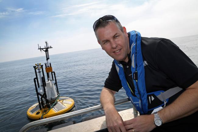 Stuart Grant, project manager for the failed Navitus Bay wind farm bid, beside a data gathering buoy in 2015