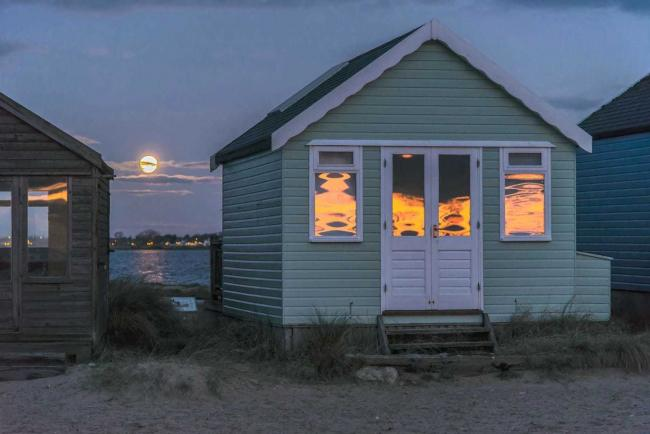 The moon setting in the background and the burning reflections of sun rising on the windows of the beach huts at Mudeford Spit taken by Echo Camera Club member Jeremy Mayes.