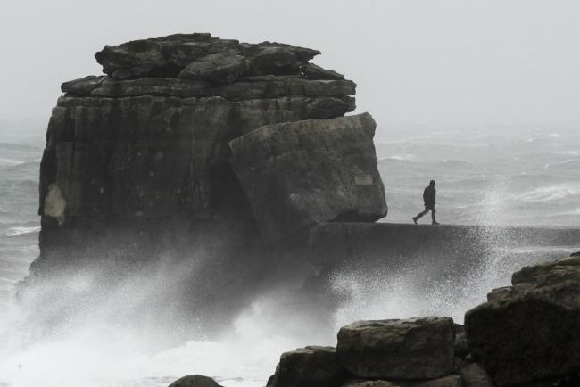 A thrill seeker at Pulpit Rock, Portland Bill during Storm Ciara. Image: Graham Hunt Photography..