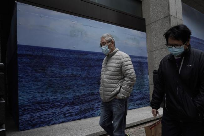 People wearing protective face masks walk on a street in the Central, the business district of Hong Kong