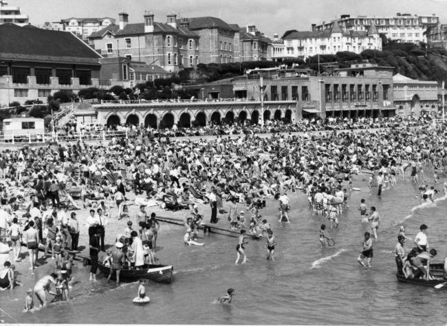 A crowded Bournemouth beach on August 26, 1978. In the background are the promenade buildings as they once looked, as well as the municipal swimming baths