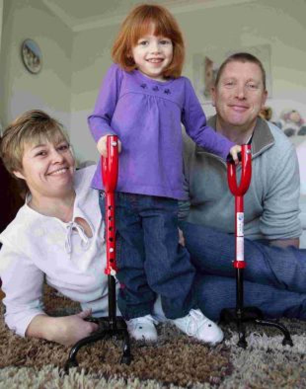 OPERATION: Charlotte Wakefield, three, back at her Corfe Mullen home with her mother and father Kim and Steve after surgery in the USA to stretch muscles in her legs