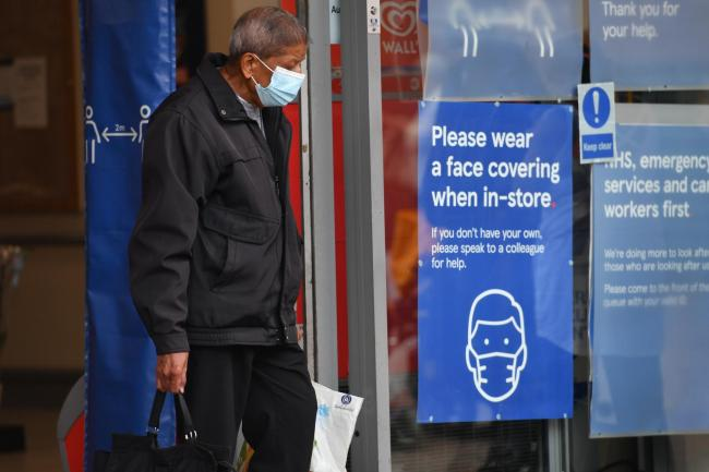 A shopper wearing a face mask leaves Tesco in Leicester city centre as non-essential shops in the city reopen following a local lockdown (Jacob King/PA)
