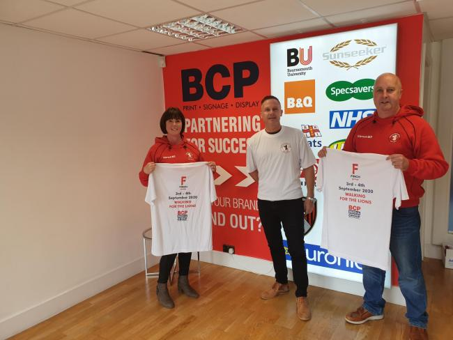 Operations Manager Wendy King and Merchandise Manager Paul Chapman, right, receiving printed t-shirts from BCP Media managing director Ian Shenton ahead of Paul's fundraiser