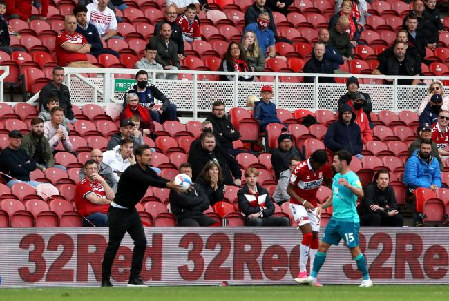 AFC Bournemouth manager Jason Tindall throws the ball back into play as fans watch in the stands where up to 1000 spectators are expected to attend during the Sky Bet Championship match at the Riverside Stadium, Middlesbrough. PA Photo. Picture date: Satu