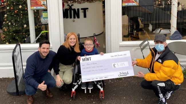 "Mint Barbers of Westbourne Director CJ Bell presenting the cheque for £3,105 to Chester and his family from their ""Trims4Chester"" event"