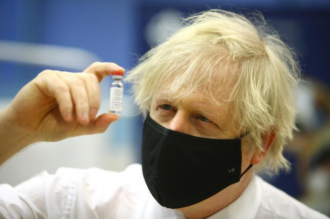 File photo dated 17/2/2021 of Boris Johnson holding a vial of the Oxford/Astra Zeneca Covid-19 vaccine. The Prime Minister has set a new target to vaccinate all adults aged over 50 - as well as those with underlying health conditions which put them at