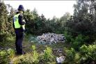 A policeman surveys the debris left behind by travellers who were served with an eviction notice to leave Stoney Cross in the New Forest