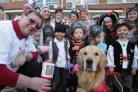 Monty, a two-year-old golden retriever in his final stage of training to be a Woofability dog, with his trainer Ray Bryan and children from the Sunshine Nursery and pupils from the Bournemouth and Poole College site