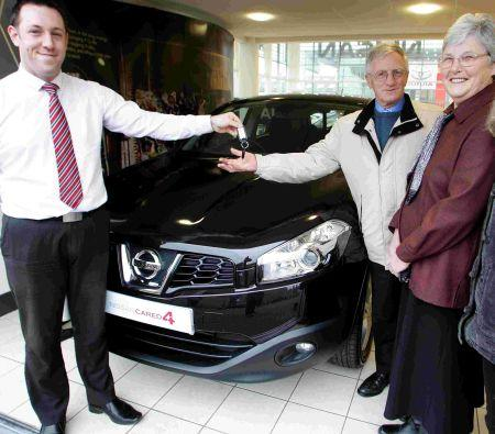 Westover Nissan sales assistant Paul Mannell presents the car keys to Ann and Andrew Jones