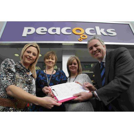 Robert Syms MP signs a petition to save the Peacocks chain of stores earlier this week. He is pictured with branch manager Leanda Leighton and staff members