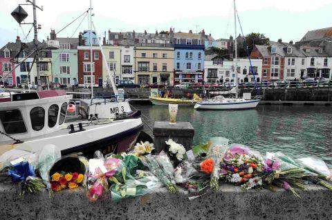Bournemouth Echo: SADLY MISSED: Floral tributes to the three fishermen are laid at the vacant berth of the Purbeck Isle on Weymouth harbourside
