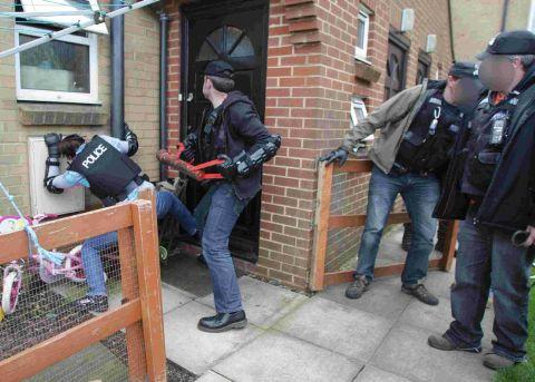 SMASH: Police officers raid a ground-floor flat in the Southbourne area of Bournemouth as part of Operation Dismantle