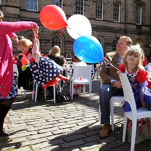 Five-year-old Amelia Paris (seated) with mother Lisa swinging her sister Elizabeth at a street party on the Royal Mile in Edinburgh