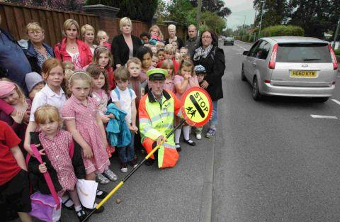 PROTEST: Pupils and parents outside St Mary's First School in West Moors with lollipop man Peter Walker