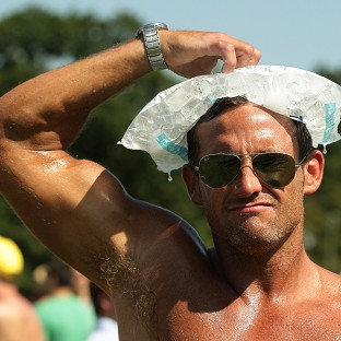 A man cools down with an ice-pack at the V Festival in Hylands Park, Chelmsford