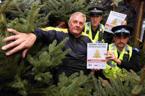 TREE FELLAS: PC Simon Hallam, rear, and PCSO Steve Willis with Vic Plowman at Plowmans Garden Centre