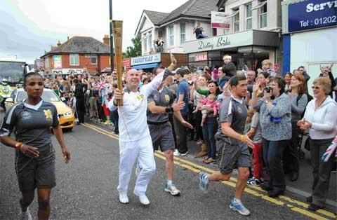 Robert Morris runs the Olympic torch in Moordown