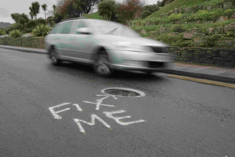A frustrated driver paints round a pothole after last winter's storms