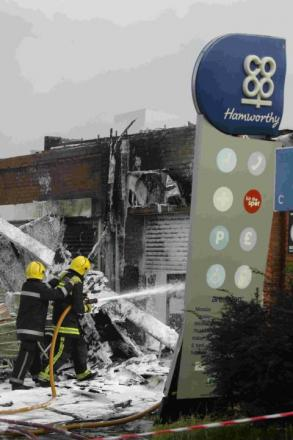 Fire officers at the scene of a blaze which destroyed the Co-op store