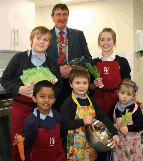 COOKS OF THE FUTURE: Dr David Rogers, president of the Rotary Club of Christchurch, with some children eager to take part in the classes