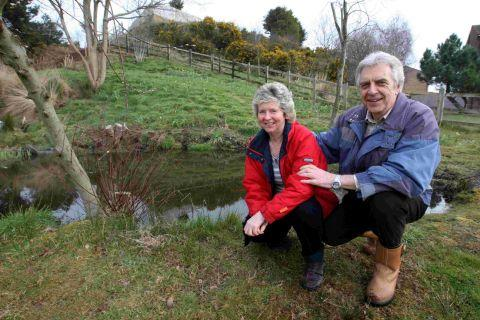 Heather and Brian Camfield by the pond in Aspen copse on the Bourne estate which they, together with other residents, have been clearing and replanting