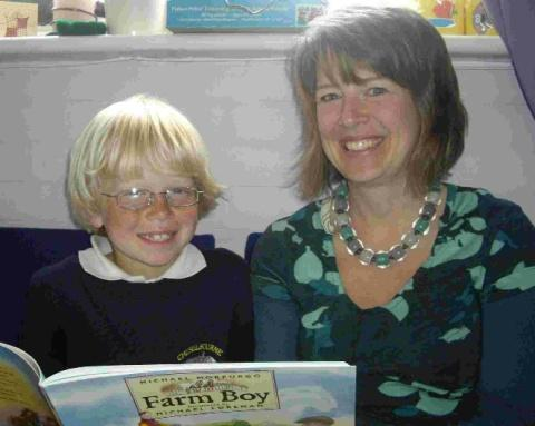 BOOK LOOK: Bonnie Stevens, a volunteer with Dorset Reading Partners helps a youngster