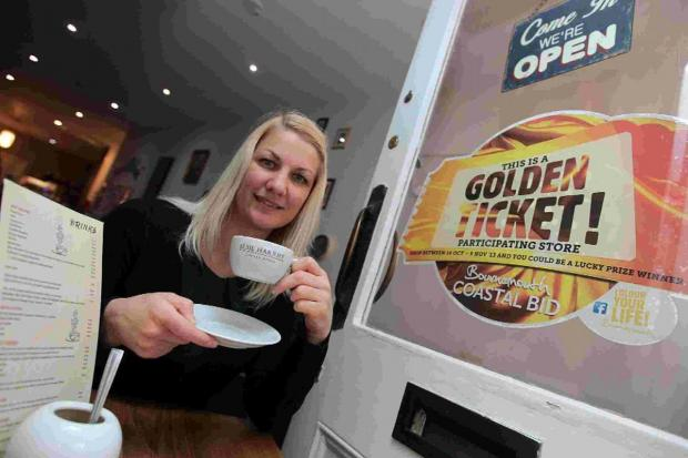 Elsie Harrhy coffee shop owner Suzanne Roycroft with her Golden Ticket logo in the window of her coffee shop