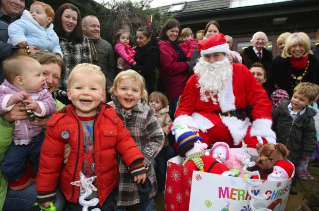 DELIGHT: Phil Carey, standing third right, with delighted children and Father Christmas, who gave out toys from the Daily Echo Toy Appeal to families at Townsend Children's Centre