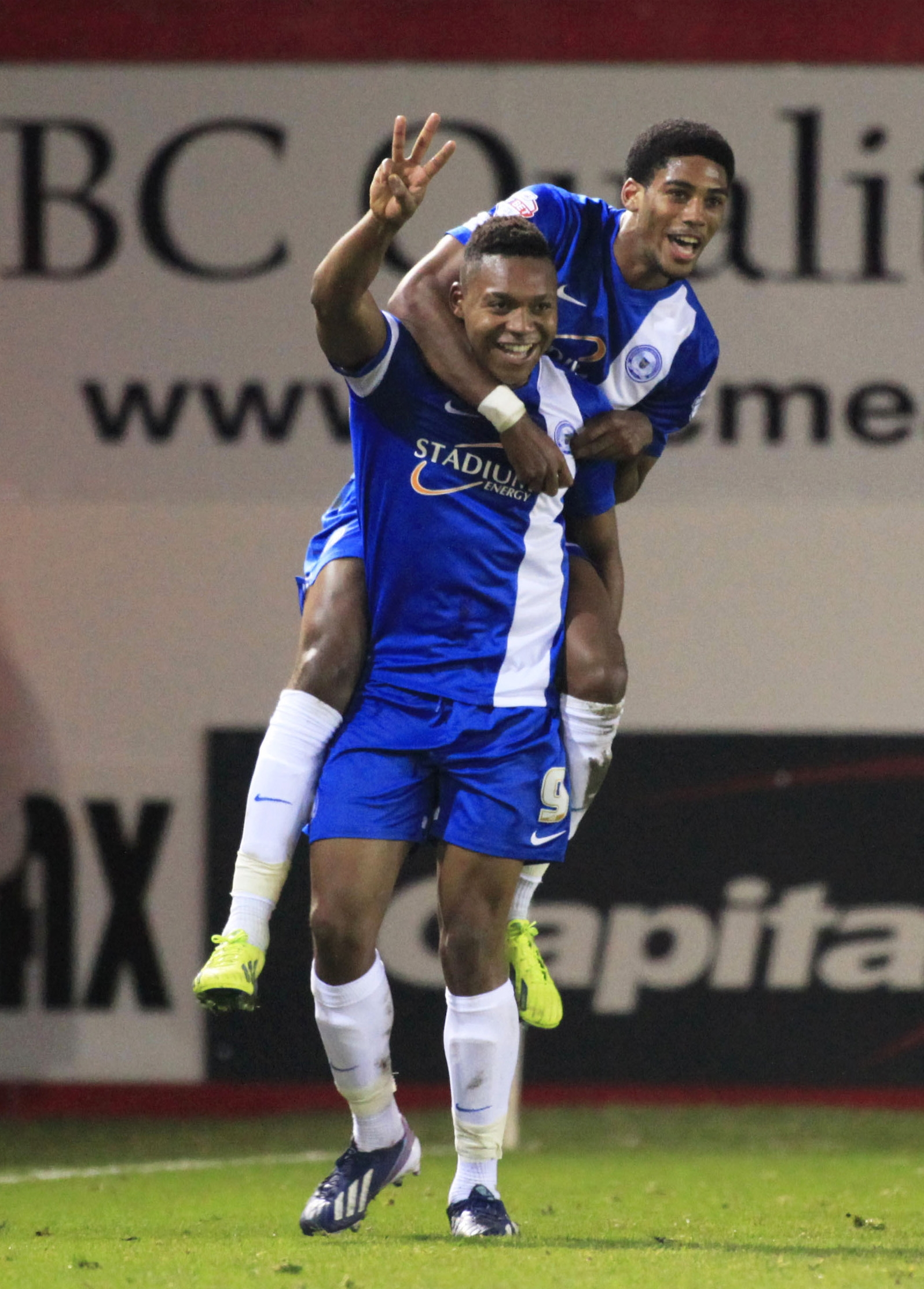 POACHER: Britt Assombalonga (standing) celebrates scoring for Peterborough last season
