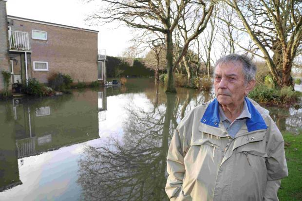 WATER RISES: Conifer Close resident Eric Matthews stands in the flood waters that now surround his block of flats