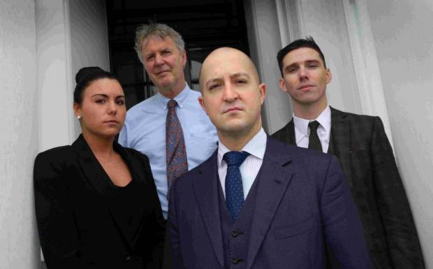 Bournemouth Echo: ACTION: Nick Robinson, front, with legal colleagues, from left, Victoria Hill, Terry Scanlon and James Moore