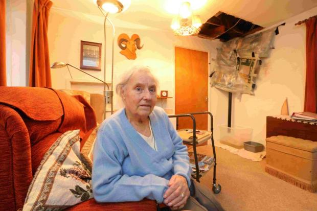 GAPING: Phyllis Rowley,85, with the hole in her lounge