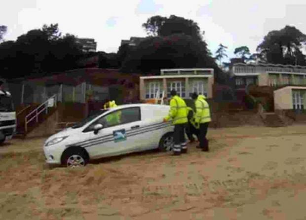 MAROONED: A screengrab taken from YouTube video of council workers trying to move their vehicle which got stuck in the sand during a clean-up on Poole's beaches