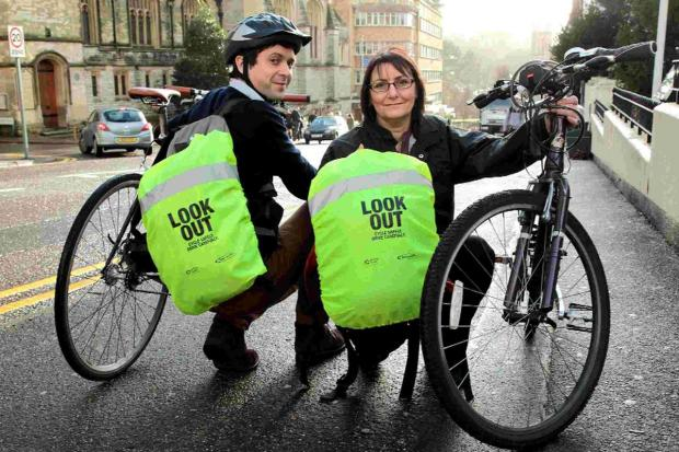 BRIGHT IDEAS: Pat Gough and Sarah Lawrence show off the free fluorescent rucksack covers