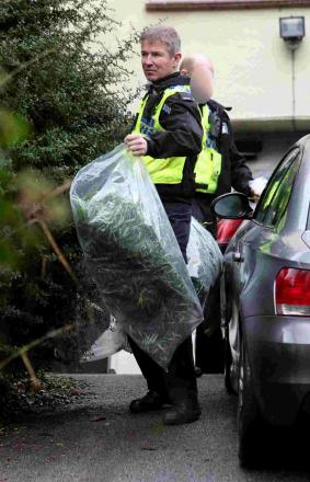 HAUL: A police officer leaves the address with two large bags full of cannabis plants