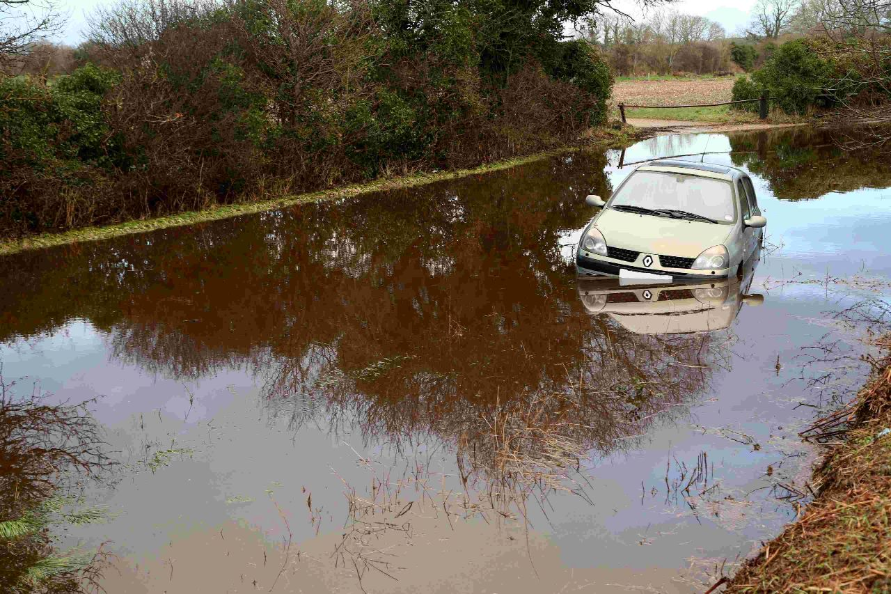 Drivers ignore warning signs and chance flood water – despite half-submerged car