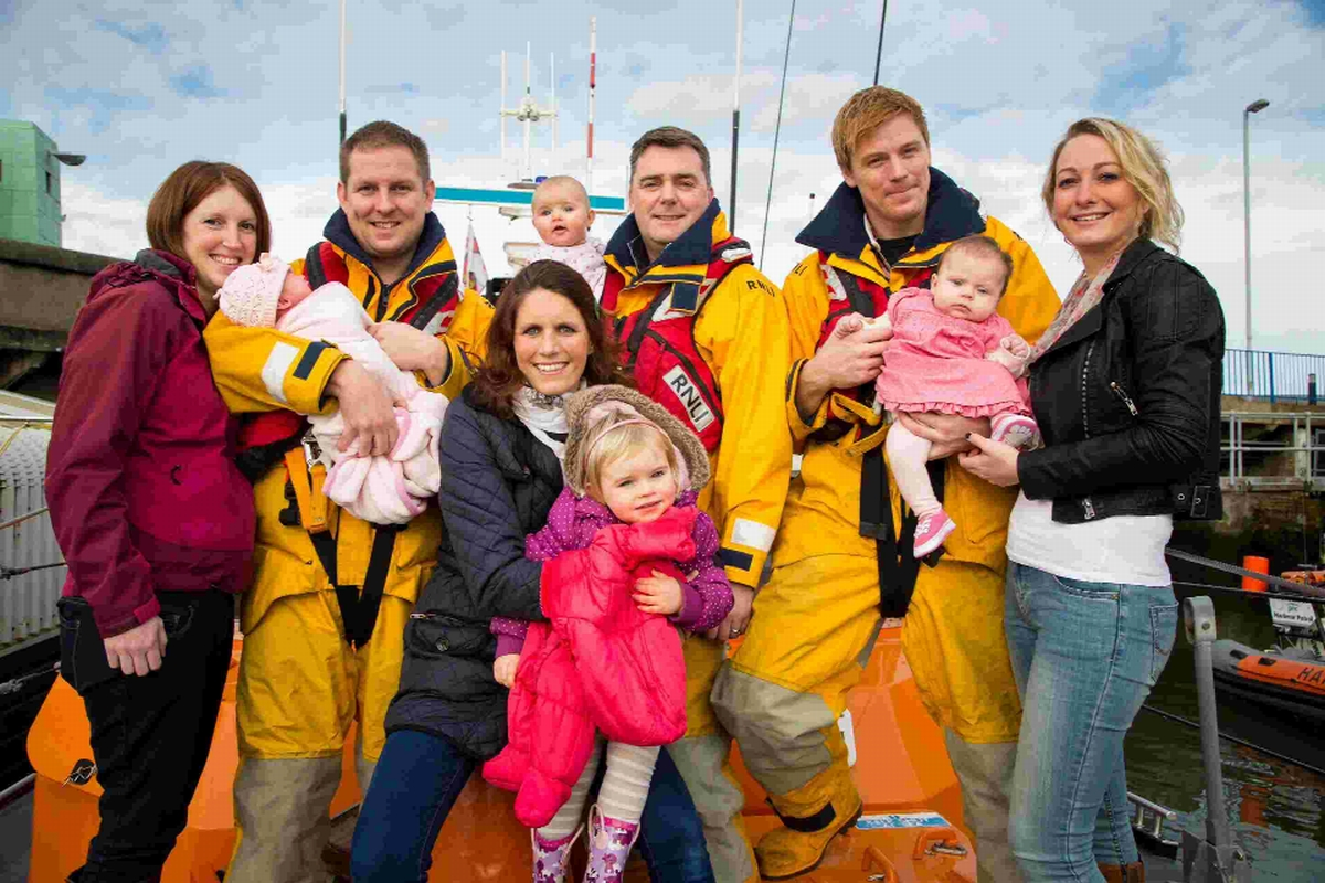 Members of the lifeboat crew and their partners show off their new arrivals at an RNLI coffee morning in Poole