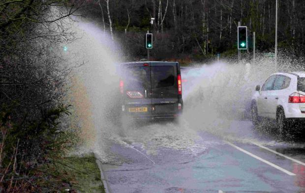 BIG SPLASH Motorists pass through standing flood water at Blackwater Junction in Bournemouth