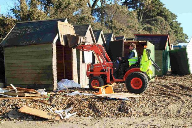The operation to clear debris continues after storms damaged beach huts along the coast