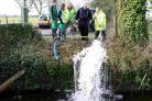 Volunteers  pump water from Derrit Lane  which has been flooded for weeks