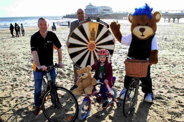 Bournemouth Echo: Giles Crist and Rob Benepal from Bournemouth Round Table, four-year-old Annabelle Corbett and a bear on a bike!