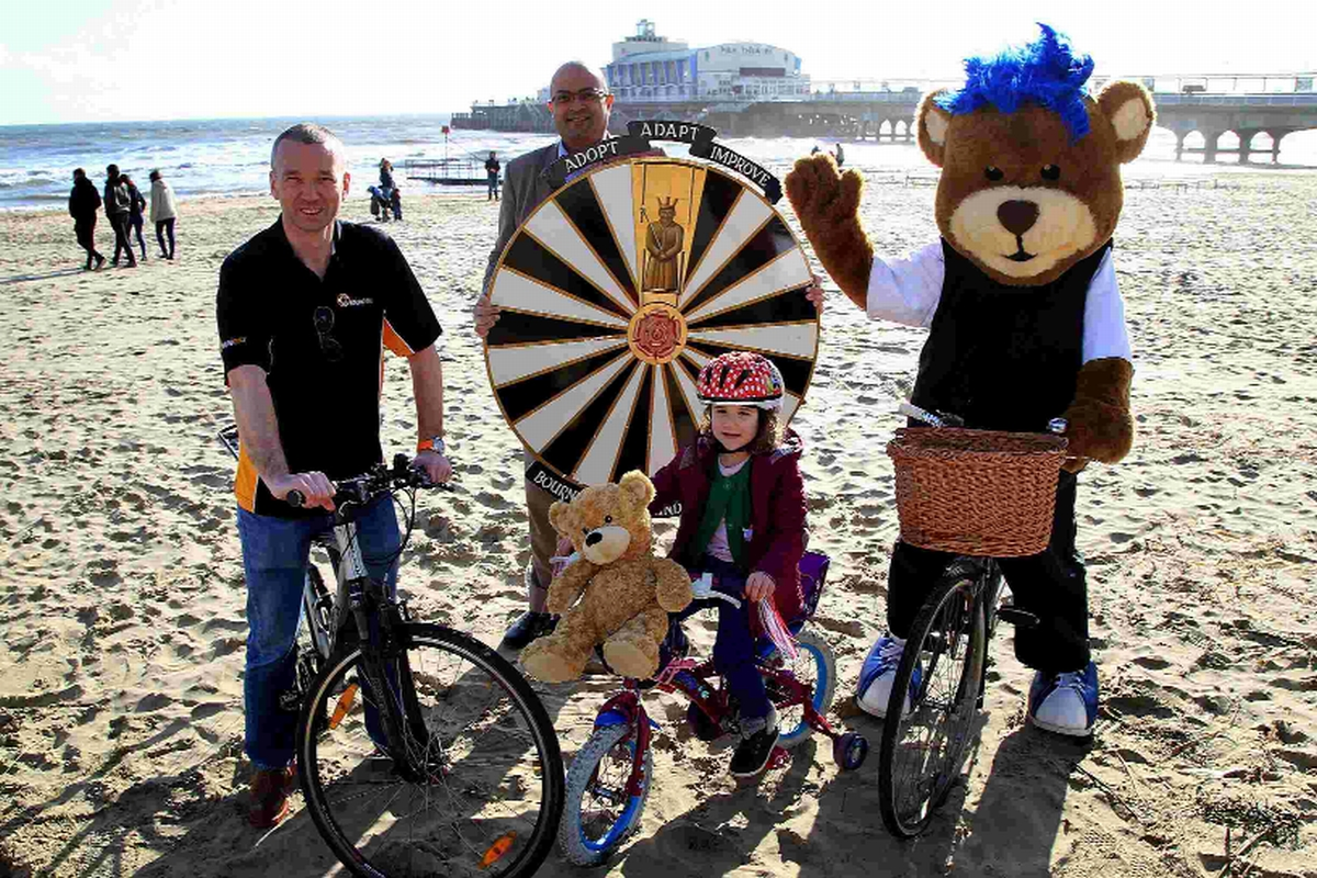 Giles Crist and Rob Benepal from Bournemouth Round Table with four-year-old Annabelle Corbett and a bear on a bike!