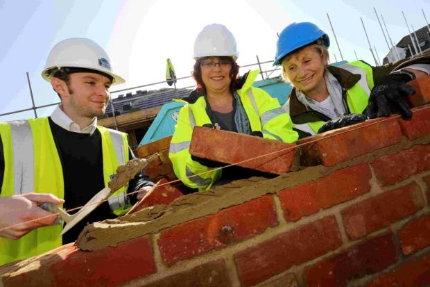 BRICK IN THE WALL: Cllr Jane Kelly, right, with Bournemouth 2026 trust development manager Debbie Clifton and site manager Dale Miller
