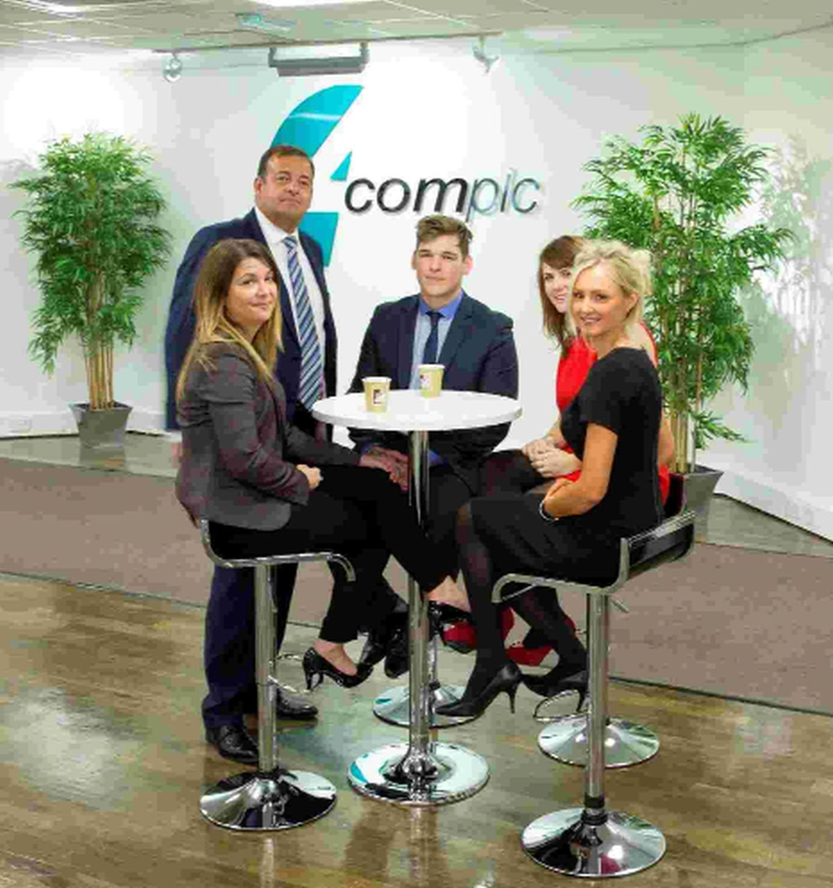 GOOD NEWS: Daron Hutt, chairman of business telecoms company 4Com, with staff