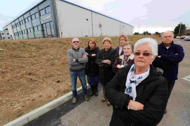 FIGHTING FIT: Linda Clarke, Chair of the Grange Residents' Association, with members beside a warehouse that sits behind houses on Grange Road