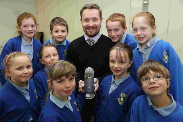 IN FINE VOICE: Headteacher of St James First School in Alderholt, Andy Poole works with pupils on a new recording