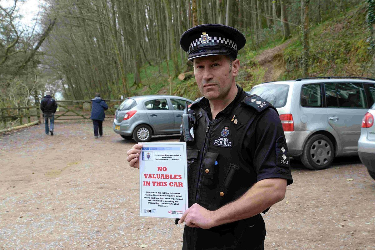 Insp Mike Darby at Langdon Wood with a sign warning visitors about car thefts