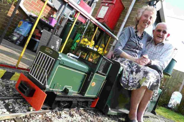 LOVE TRAIN: Mike Le Brocq and his wife Merle on the model railway they have built in the garden of their home